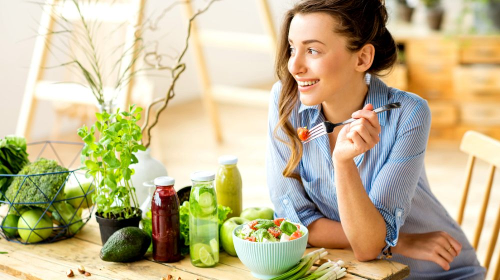 young happy woman eating healthy salad | Ways To Do A Body Detox | Makeup Tutorials | featured
