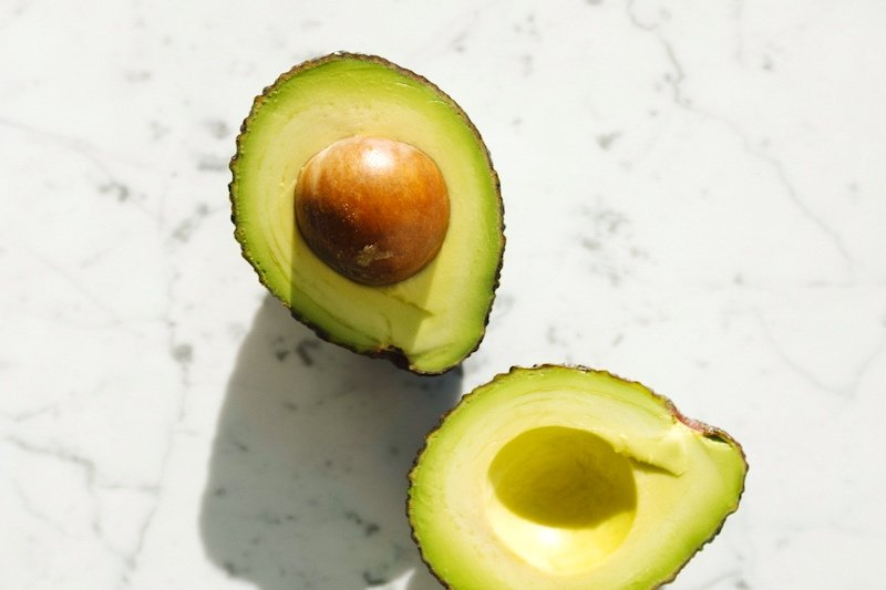halves of fresh green avocado on marble surface tanning oil | Homemade Tanning Oil Recipe That Will Get You Ready For Summer| diy sun tanning oil
