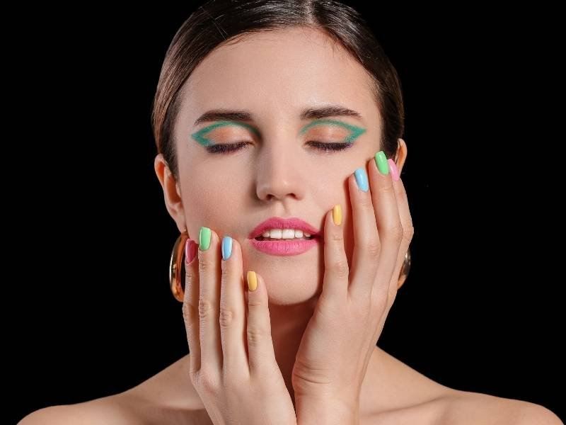 woman with green eyeliner and colorful nails | Glamorous Fall Makeup Looks To Look Forward To